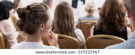 Young woman is listening at the conference  - stock photo