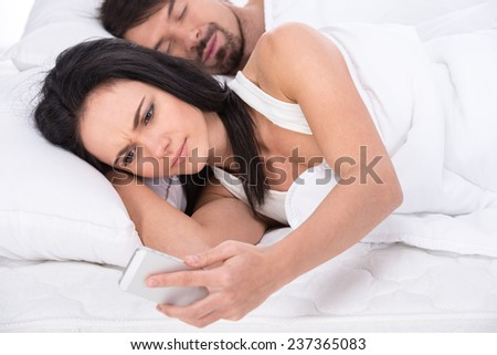 Young woman is looking at mobile phone while her husband is sleeping. - stock photo
