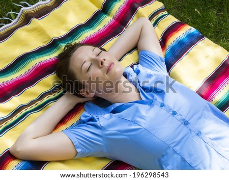 young woman is lying on a blanket on grass and sleeps - stock photo