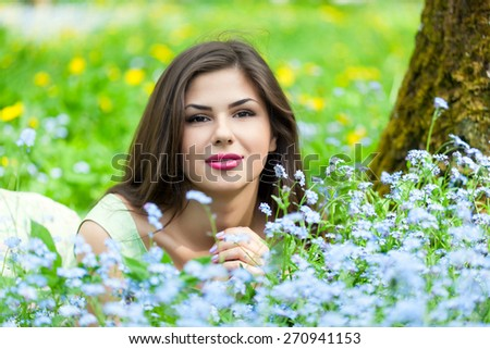 Young woman is lying on field with forget-me-not - stock photo