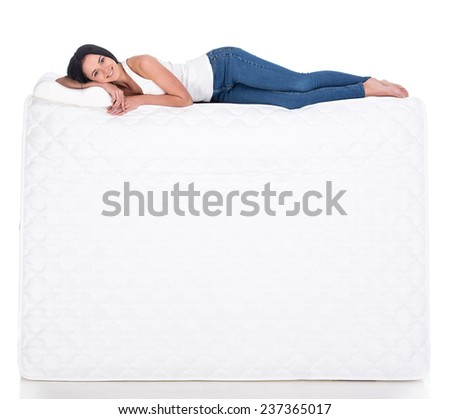 Young woman is lying on the mattress. Isolated on white background. Side view. - stock photo
