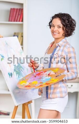 Young woman is painting a picture. - stock photo
