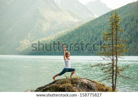 Young woman is practicing yoga at mountain lake - stock photo