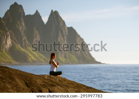 Young woman is practicing yoga between mountains in Norway - stock photo
