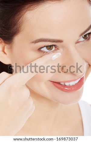 Young woman is putting eye lens.  Isolated on white. - stock photo