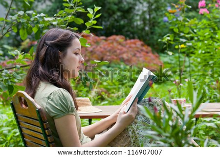 Young woman is reading in a garden - stock photo