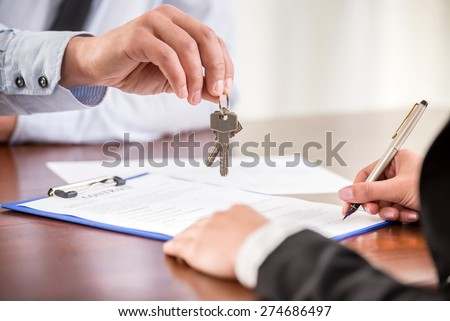 Young woman is signing financial contract with male realtor. Close-up. - stock photo