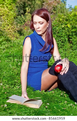 young woman is sitting on green grass reading a book and holding an apple in her hand - stock photo