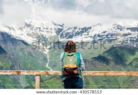 Young woman is standing at viewpoint and looking beautiful mountain landscape. Hiking female tourist with backpack relaxing on the top enjoying spectacular view. - stock photo