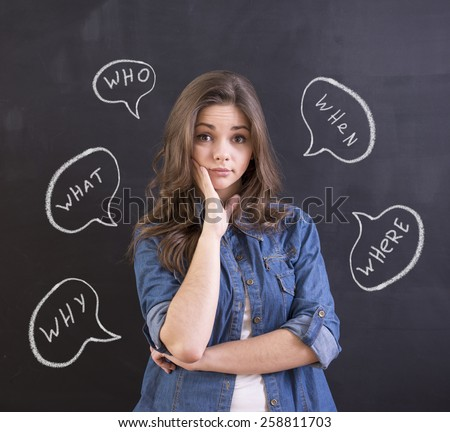 Young woman is standing in front of blackboard background with question. - stock photo