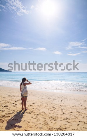 young woman is standing on beach - stock photo