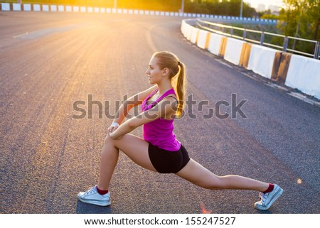 young woman is streching outdoors - stock photo