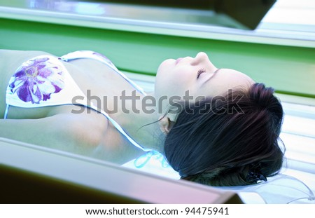 Young woman is tanning in solarium. - stock photo