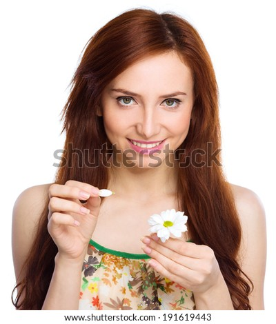 Young woman is tearing up daisy petals, isolated over white - stock photo