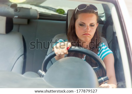 Young woman is trying to turn the broken car on - stock photo