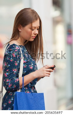Young Woman is using phone on the street - stock photo
