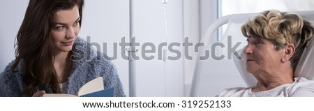 Young woman is visiting her grandmother and reading a book - stock photo