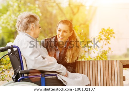 Young woman is visiting her grandmother in nursing home - stock photo