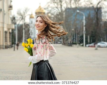 Young woman is yellow tulips flowers in the city.  Mindfulness, facial expression, emotions. Spring walking and lifestyle. - stock photo