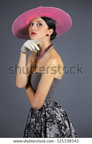 Young woman isolated on gray vintage hat and style - stock photo