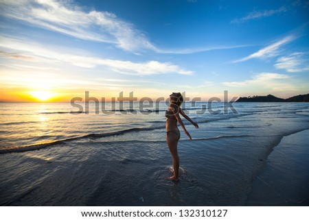 Young woman jogger at sunset on the seashore. - stock photo