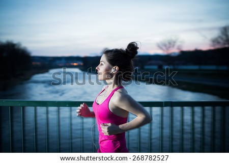 Young woman jogging at night in the city on the bridge cross the river. Girl running outdoors in a city park. Motion blurred image. Color toned image.  - stock photo