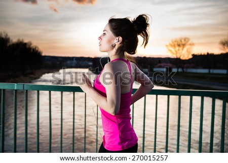 Young woman jogging at sunset in the city on the bridge cross the river. Girl running outdoors in a city park. Color toned image. - stock photo