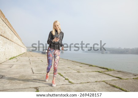 Young woman jogging by the river and listening to music on her smart phone - stock photo