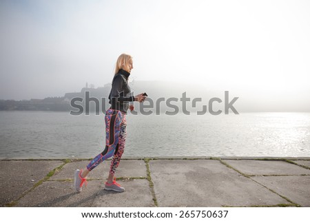 Young woman jogging by the river on a cold misty morning and listening to music on her mobile phone - stock photo