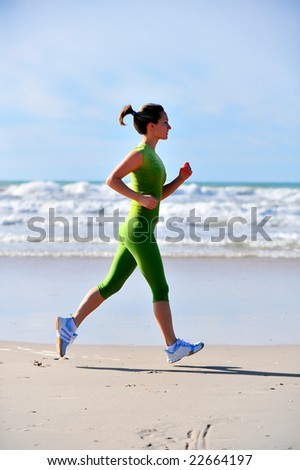 young woman jogging on the beach at sunrise - stock photo