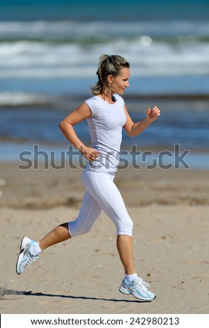 young woman jogging on the beach in summer sunny day - stock photo
