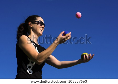 Young woman juggler is juggling balls.  concept photo of flexibility, success, skill and control. - stock photo