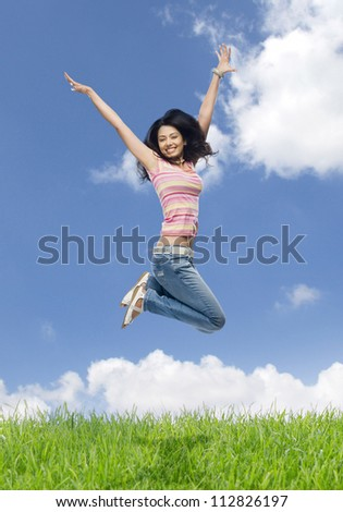 Young woman jumping in a field - stock photo