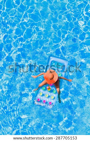 Young woman jumping in the buoy at the swimming pool - stock photo