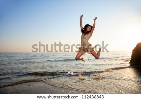 Young woman jumping on a beach in the summertime - stock photo