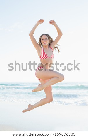 Young woman jumping on the beach wearing a red bikini smiling at camera - stock photo