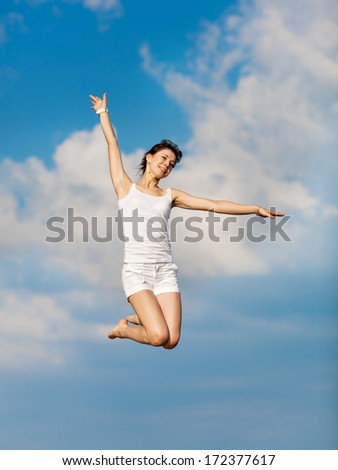 Young woman jumping outdoors. Girl in white hopping with arm raised on background of sky - stock photo