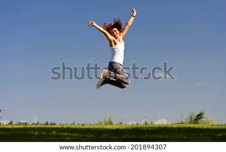 Young woman jumping outside - stock photo