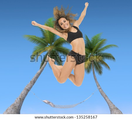 Young woman jumping with a hammock tied to two palm trees and a blue sky in the background - stock photo