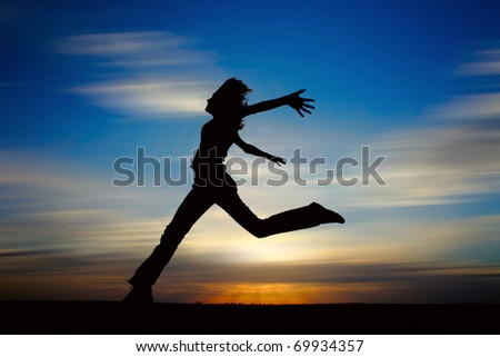 Young woman jumping with raised hands. - stock photo