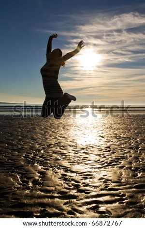 Young woman jumping with raised hands on the beach - stock photo
