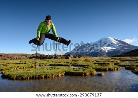 Young woman jumps and enjoys beautiful view into high mountains, Chimborazo volcano, Ecuador, Andes, South America - stock photo