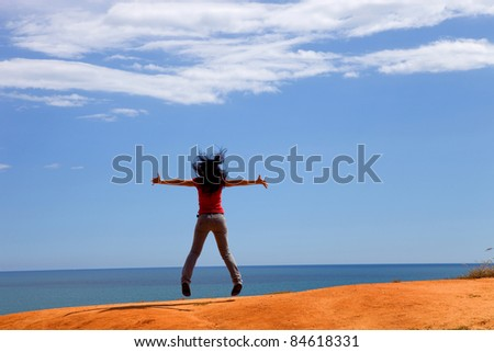 young woman jumps with arms wide open at the coast - stock photo