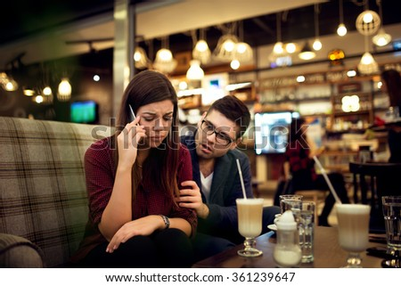 Young woman just found out some bad news. Her boyfriend is consoling her. - stock photo