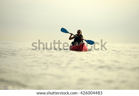 Young woman kayaking in ocean 