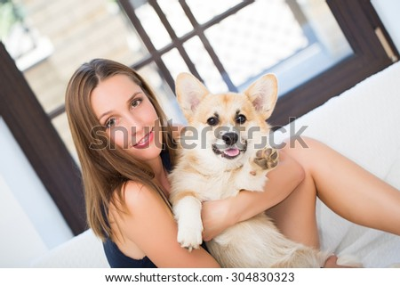 Young woman keeping welsh corgi  puppy  near her face  - stock photo