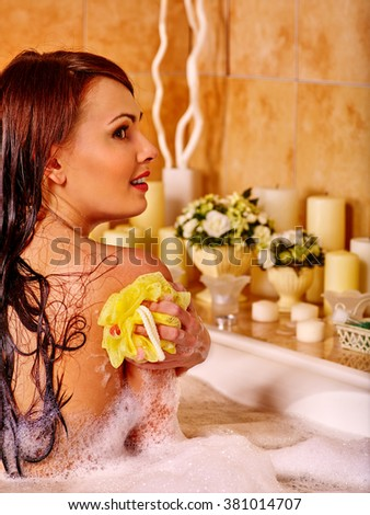 Young woman keeps sponge take bubble  bath. Woman washing her shoulder. - stock photo