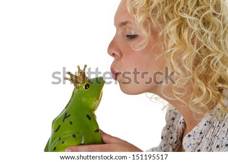 Young woman kissing a frog prince isolated on white background - stock photo