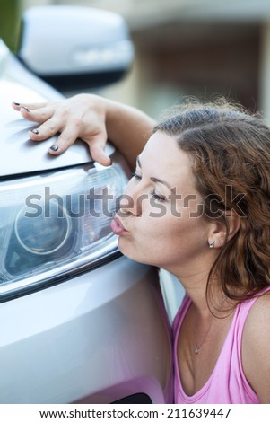 Young woman kissing her new car - stock photo