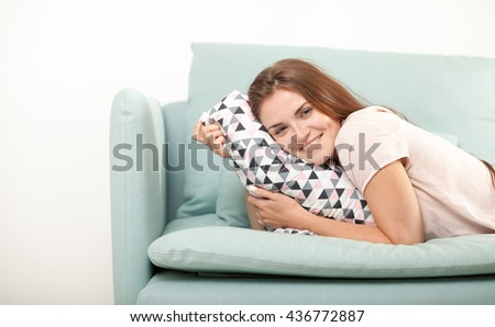 Young woman laughing and lying on couch at home, domestic style shoot - stock photo